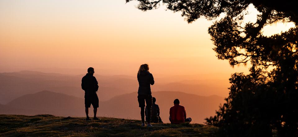 A group of people meet the sunrise at the peak of the mountain