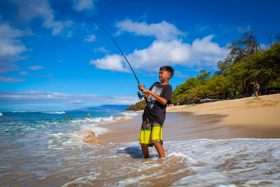 Kid fishing on the shore in Hawaiian Islands